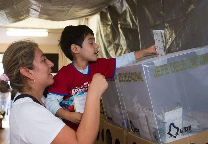Según Martí Batrtes, el Partido Morena se convirtió en la primera fuerza política del DF. En la imagen, una mujer permite que su hijo deposite el voto en las urnas. (Notimex)