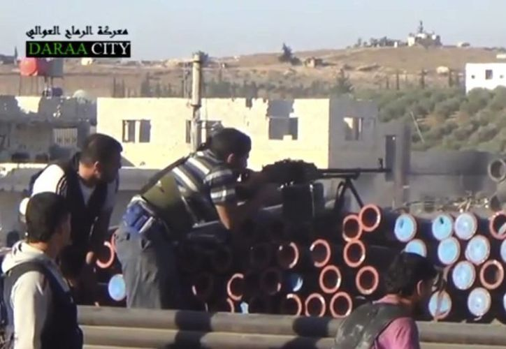 Rebeldes sirios disparan contra las fuerzas del gobierno en Daraa al-Balad. (Agencias)