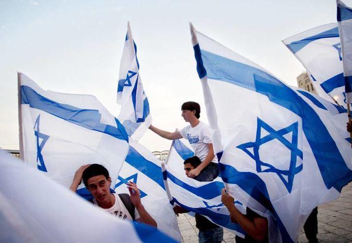 En esta foto del 2011, jóvenes israelíes danzan con banderas nacionales antes de orar ante el Muro de los Lamentos. (Foto de contexto. Archivo Agencias)
