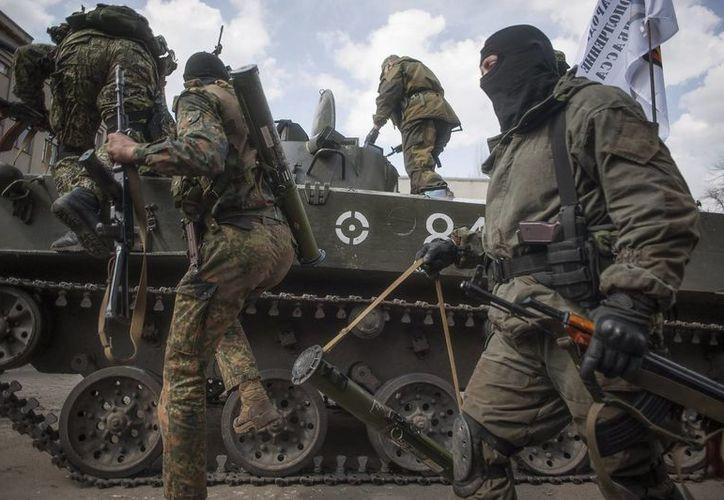 Prorrusos armados y vestidos con trajes militares se suben a un tanque en Slovyansk, en la región de Donetsk, Ucrania. (EFE)