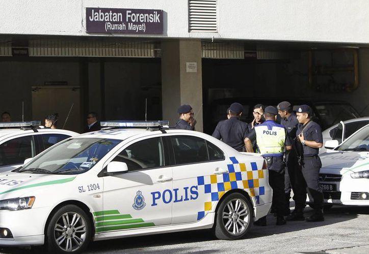 Kim Jong Nam, el hermanastro del líder norcoreano Kim Jong Un, fue asesinado este lunes en un aeropuerto de Kuala Lumpur. Imagen de contexto de un grupo de policías en el hospital de Putrajaya, Malasia, lugar donde se encuentra su cuerpo. (Foto AP / Daniel Chan)