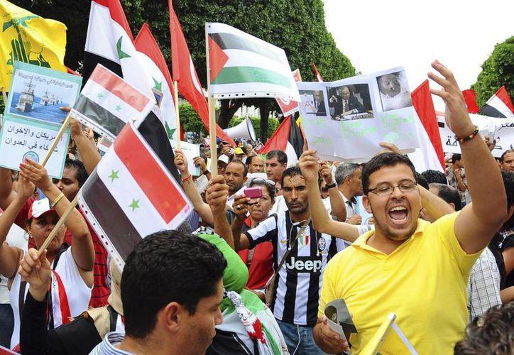Manifestantes ondean banderas sirias y de Túnez durante una manifestación contra el posible ataque de EU en Siria. (Agencias)