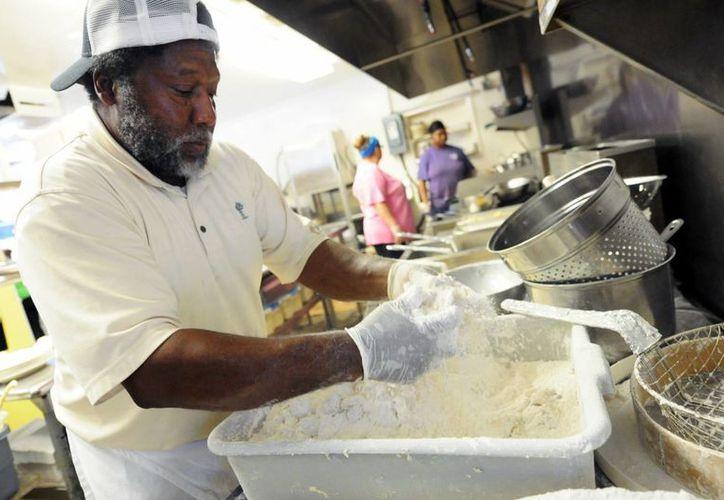 Andy Gause prepara un platillo a base de camarones en el restaurante Calabash Seafood Hut en Carolina del Norte. El crecimiento económico de EU ayuda a los empresarios a contratar más personal. (Agencias)