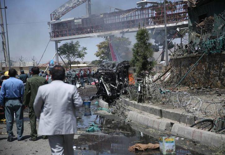 Fuerzas de seguridad afganas observan el lugar de un atentado ante la puerta principal del aeropuerto internacional de Kabul, en Afganistán. (Agencias)