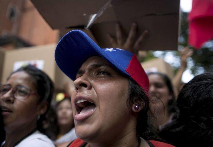 Estudiantes gritan contra la Policía Nacional Bolivariana que les impide el paso durante una protesta contra el presidente Maduro, en Caracas, Venezuela. (AP/Alejandro Cegarra)