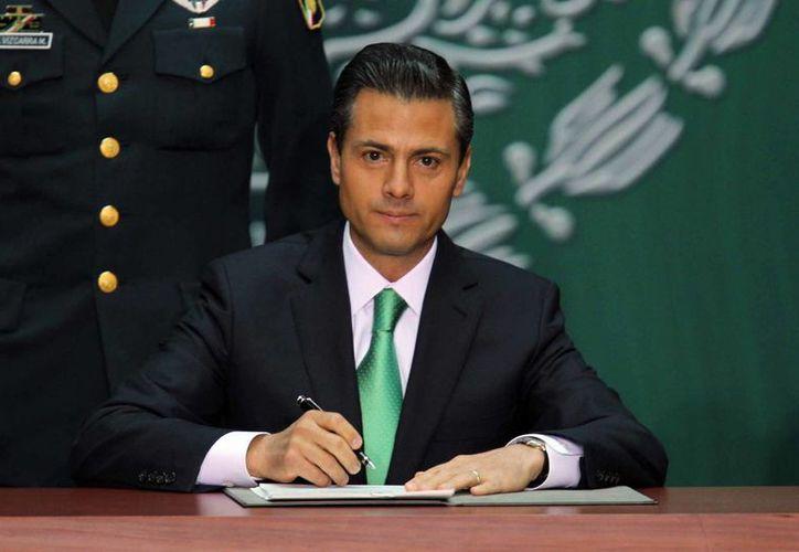 El presidente Enrique Peña Nieto durante la firma correspondiente a la promulgación de la Reforma Energética, este viernes. (Notimex)