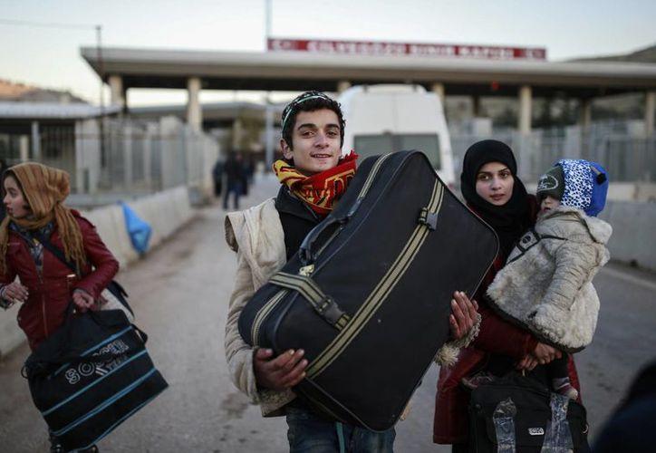 Miembros de una familia siria cargan sus pertenencias tras cruzar a Turquía en el paso de frontera de Cilvegozu, cerca de Hatay, en el sudeste de Turquía. (AP/Emrah Gurel)