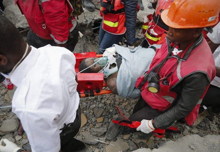 Una mujer es trasladada en camilla después de ser rescatada con vida tras permanecer seis días bajo los escombros de un edificio que se vino abajo en Huruma. (EFE)