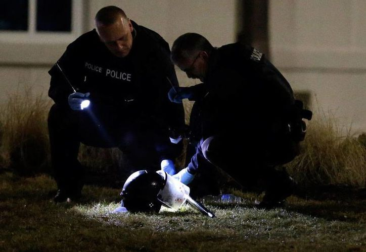 Policías revisan un casco en el lugar donde manifestantes  dispararon contra 2 policías, a las afueras de la comisaría de Ferguson. (AP)