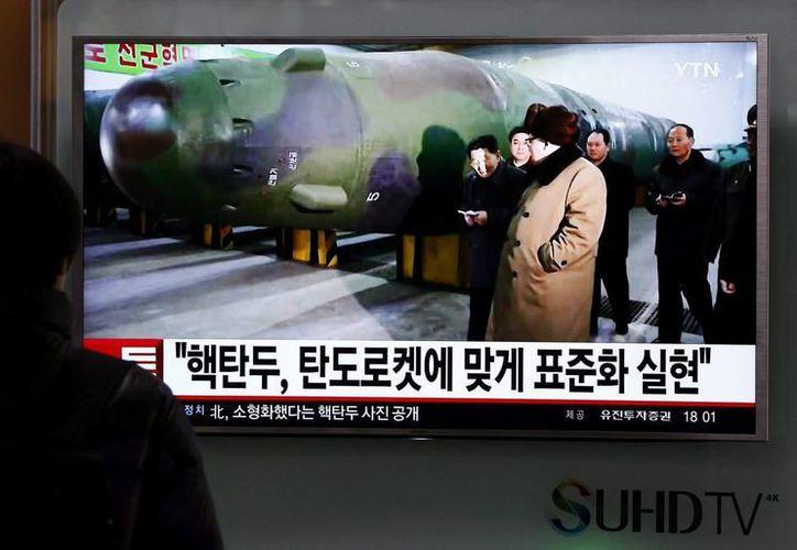 Un surcoreano observa la televisión donde se ve al líder de Corea del Norte, Kim Jong-un, junto a una réplica de una ojiva miniaturizada. (EFE/Archivo)