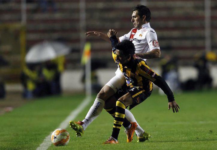 Jair Torrico, de Bolivia, y David Depetris, de México, pelean por el balón en el partido de Copa Libertadores entre Monarcas Morelia y The Strongest. (Foto: AP)