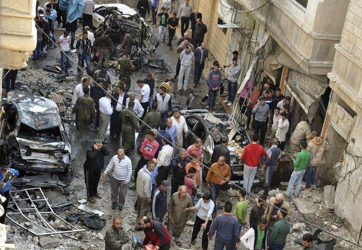 Policías y ciudadanos sirios, en el lugar donde fue perpetrado un atentado suicida con un coche bomba contra una zona de mayoría alauí. (Archivo/EFE)