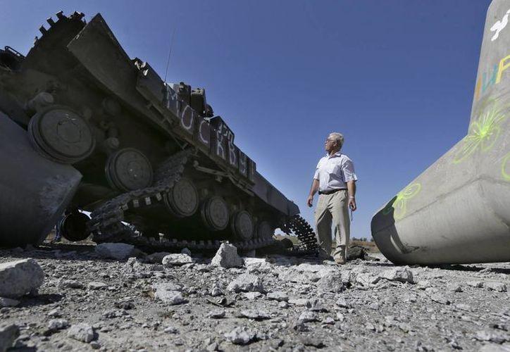 Un hombre observa un tanque de la Armada destruido cerca de la villa de Lebedynske, en Ucrania. (Foto: AP)