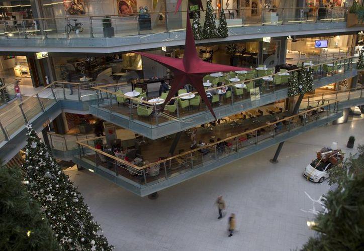 Compradores solitarios recorren un vacío centro comercial en las afueras de Amsterdam. (Agencias)