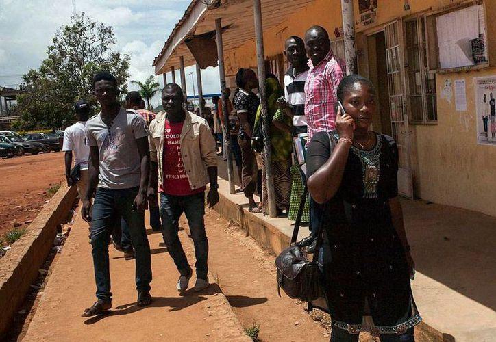 Testigos aseguraron que al menos 48 estudiantes perdieron la vida en un atentado en una escuela de Nigeria. La imageno no corresponde al hecho: se trata de estudiantes de la escuela politécnica de Jos, quienes salen del inmueble, luego de un atentado, en septiembre de 2013. (EFE/Archivo)