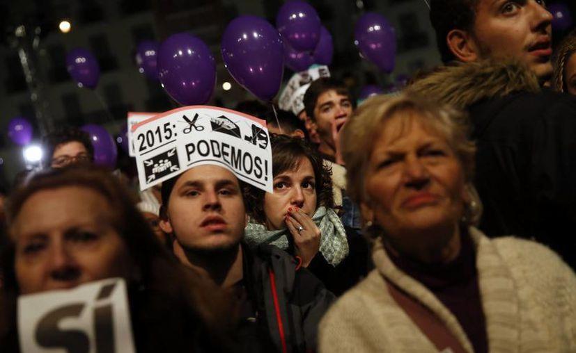 Simpatizantes del partido Podemos, durante las elecciones de este domingo en España. Esta fuerza política alcanzó los 69 escaños, un buen porcentaje que otorga una mayor pluralidad en el Parlamento a pesar de que Mariano Rajoy, del PP, haya sido reelegido como presidente. (AP)