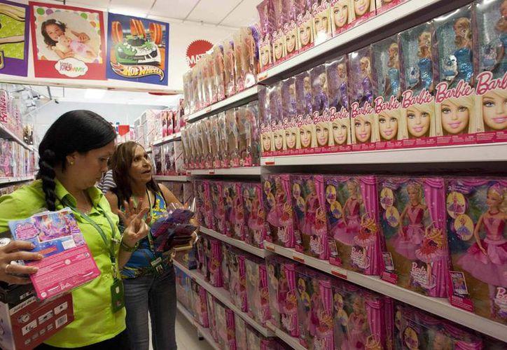 Dos mujeres seleccionan Barbies en una tienda en Caracas, Venezuela, país que abarató las icónicas muñecas. (Agencias)