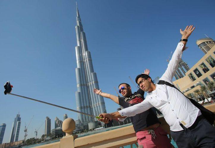 Rasul Alekberov, de Azerbayán, sostiene una vara expandible para tomarse una selfie junto a su amiga Gudrat Aghayev, mientras ambos le dan la espalda al  'Burj Khalifa', el rascacielos más alto del mundo, situado en Dubai, capital de Emiratos Árabes Unidos. (Foto: AP)