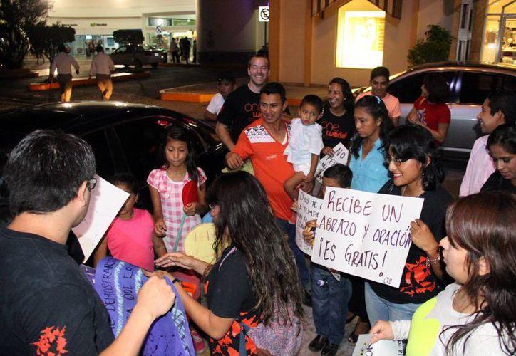 Decenas de jóvenes regalaron abrazos ayer en el estacionamiento de Plaza las Américas. (Consuelo Javier/SIPSE)