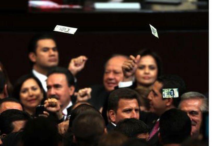 A Peña Nieto le arrojan billetes falsos a modo de confeti. (Agencia Reforma)