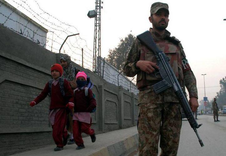 Un soldado paquistaní vigila mientras los estudiantes llegan a una escuela en Peshawar, Pakistán (Xinhua/Umar Qayyum)