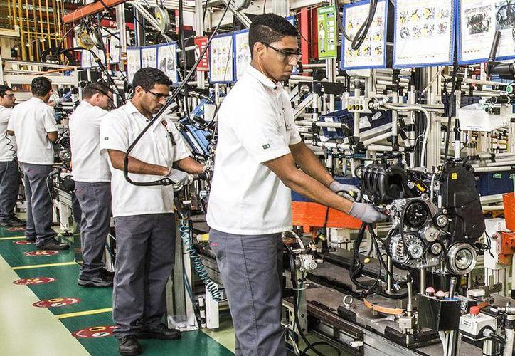 El salario mínimo destacó que por primera vez desde 1976 se recuperó en 5.1 por ciento su nivel adquisitivo. Imagen de un grupo de empleados en una fábrica de autos. (Archivo/Notimex)