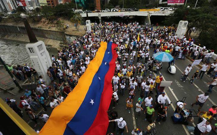 Estudiantes de universidades privadas y públicas, madres y profesionales jóvenes partieron con banderas venezolanas y pancartas desde cuatro puntos del este de Caracas. (EFE)