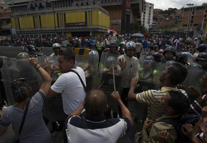 Un grupo de personas protestan frente frente a miembros de la Guardia Nacional Bolivariana y la Policía Nacional Bolivariana en Caracas. (EFE)
