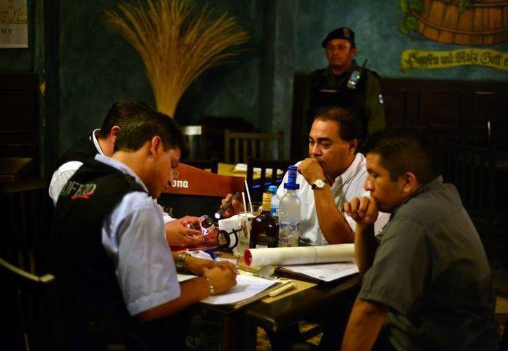 Personal de la Profeco toma datos en uno de los restaurantes incluidos en la revisión que se realizó anoche en Mérida. (Luis Pérez/SIPSE)
