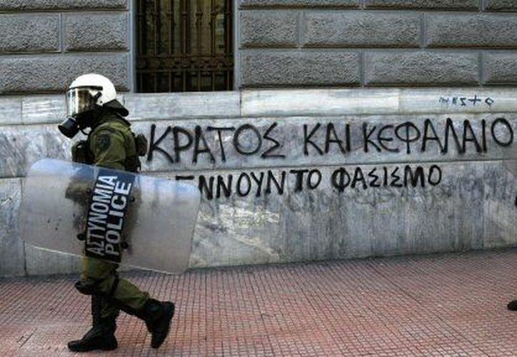 Policías griegos vigilan edificios de gobierno ante posibles manifestaciones masivas. (Agencias)