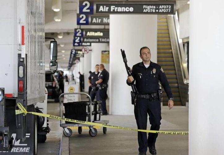 Un policía vigila la Terminal 2 del aeropuerto internacional de Los Angeles después del tiroteo que se registró ayer. (Agencias)