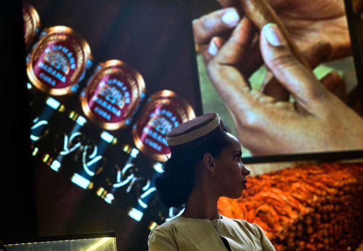 Una edecán se observa frente a un cartel del XIX Festival Internacional del Habano, un foro anual que convoca en la isla a amantes del puro, industria que es un puntal de la economía en Cuba. (AP/Ramón Espinosa)