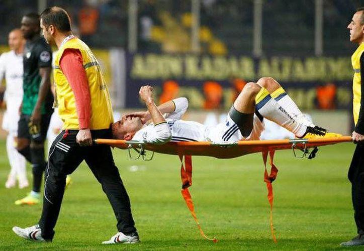 Robin Van Persie tuvo que salir en camilla tras recibir un fuerte codazo de Abdoul Sissoko, en un partido de la superliga turca.(EFE)