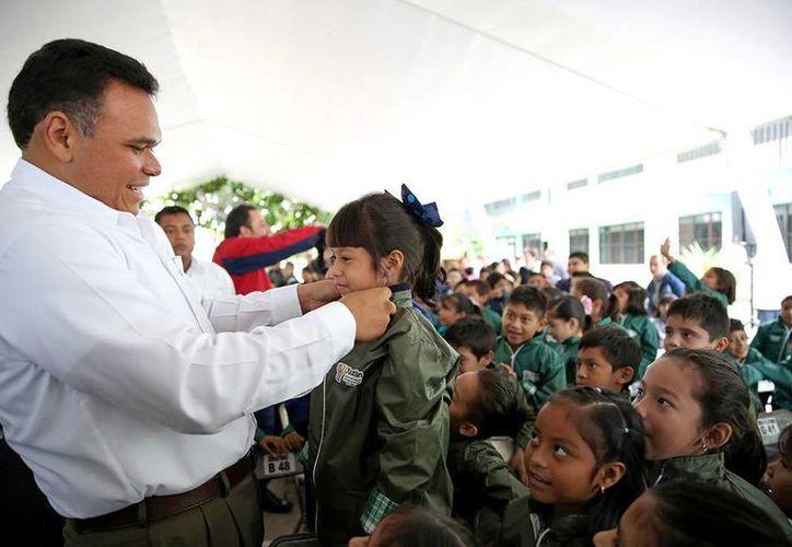 De acuerdo con el Gobierno de Yucatán, las 227 mil chamarras que regalará a estudiantes de primaria están hechas 'a la medida' de cada estudiante. En la imagen, el gobernador Rolando Zapata ajusta la chamarra de una niña de la escuela Salvador Varela Reséndiz, de Pacabtún, en Mérida. (Oficial)