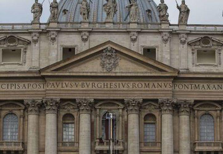 Bomberos decoran con terciopelo rojo el balcón central de la Basílica de San Pedro, en la Ciudad del Vaticano. EFE