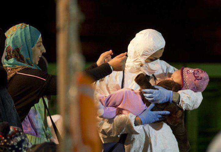 Un rescatista carga a uno de los niños que viajaban en el buque que naufragó en la costa de Libia. (Agencias)