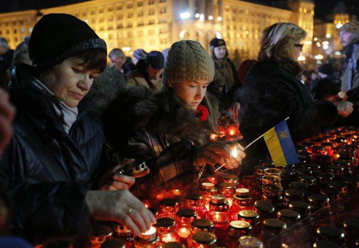 Ucranianos encienden velas durante un acto en Kiev, Ucrania, para marcar el aniversario de las protestas que concluyeron con la caída del gobierno del presidente Víktor Yanukovich. (Agencias)