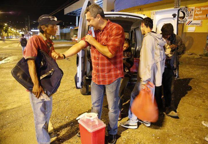 Hugo Castro, trabajador social del programa Cambie, muestra a un heroinómano cómo hacerse correctamente un torniquete en el brazo para encontrar la vena para inyectarse la droga. (Agencias)