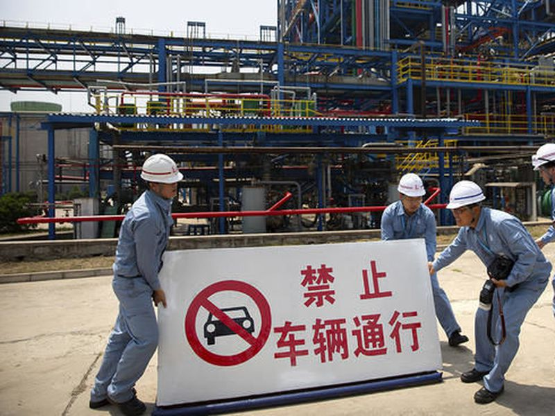 Workers move a sign near facilities for producing polypropylene at the Sinopec Yanshan Petrochemical Company on the outskirts of Beijing.