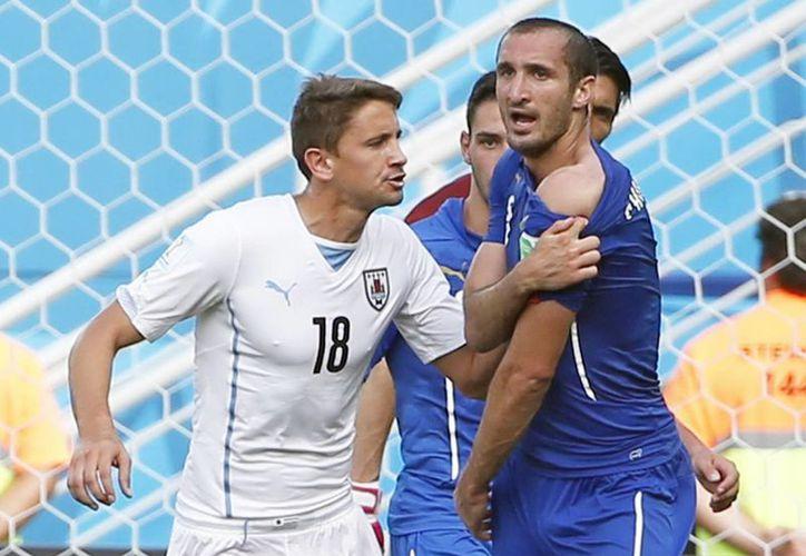 Chiellini se destapó un hombro para que el árbitro viera la mordida que le ocasionó Luis Suárez, pero ahora sale a defender al delantero uruguayo. (EFE)