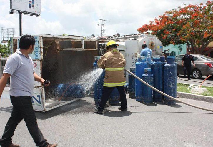 Los bomberos arrojaron espuma sobre los tanques de gas butano. (Martín González/SIPSE)