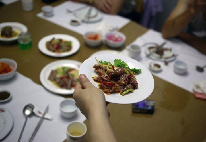 Un mesero sirve un platillo hecho con carne de perro en el restaurante House of Sweet Meat, especializado en carne de perro, en Pyongyang, Corea del Norte el miércoles 25 de julio de 2018. (AP)