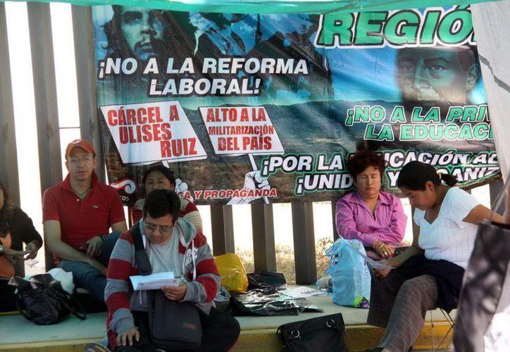 Profesores de la Sección 22 del SNTE acordonaron el Congreso de Oaxaca y se instalaron en plantón indefinido. (Notimex)