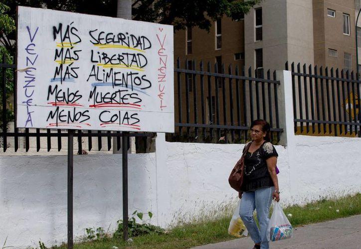 """Una mujer camina por un cartel que dice """"Venezuela, más seguridad, más libertad, más comida, menos muertes, menos colas"""" cerca de la barriada de Petare en Caracas, Venezuela. (Agencias)"""