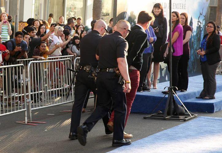 Dos oficiales alejan a Vitalii Sediuk del Teatro El Capitán, después de que se abalanzara sobre Pitt. (Agencias)