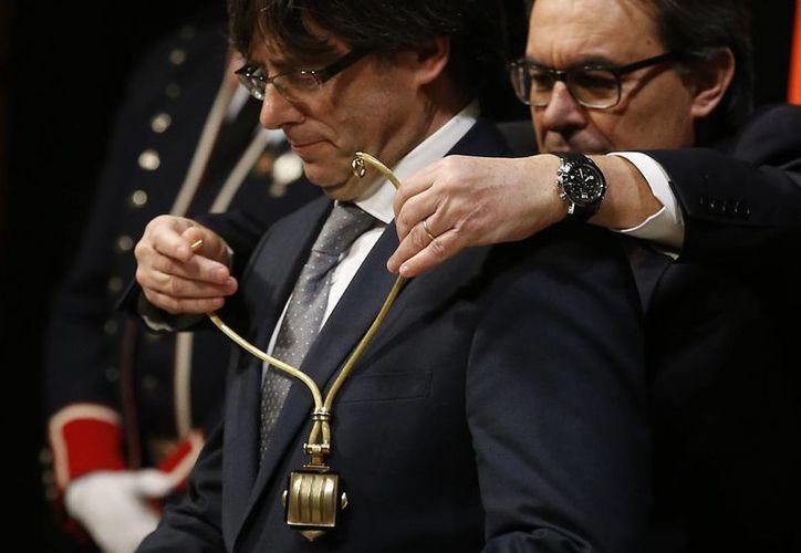 Carles Puigdemont recibe el collar que lo acredita como Presidente de la Generalitat de Cataluña de manos de su antecesor, Arthur Mas, este martes en Barcelona. (AP)