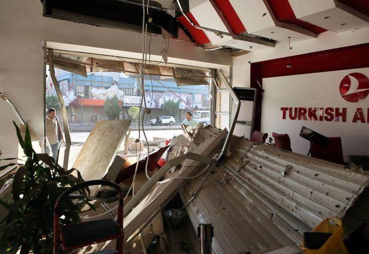 Civiles iraquíes examinan los daños causados por un coche bomba en una oficina de Turkish Airlines en Saadoun, Bagdad. (Agencias)