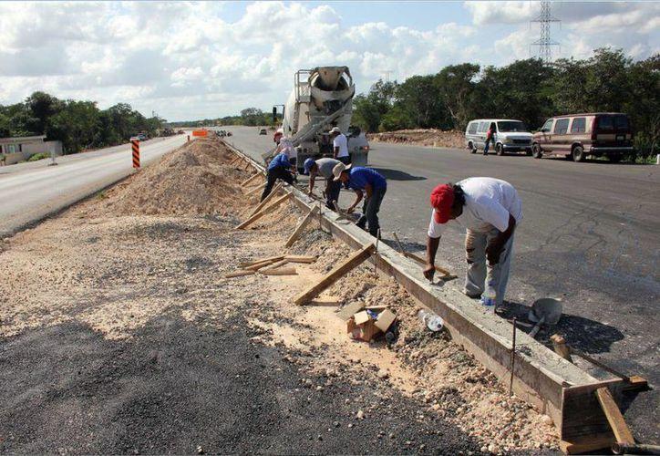 Sugieren al Estado hacer recortes en gastos y no en la obra pública. Imagen de un grupo de trabajadores en la construcción de guarniciones en una carretera del Estado. (Milenio Novedades)