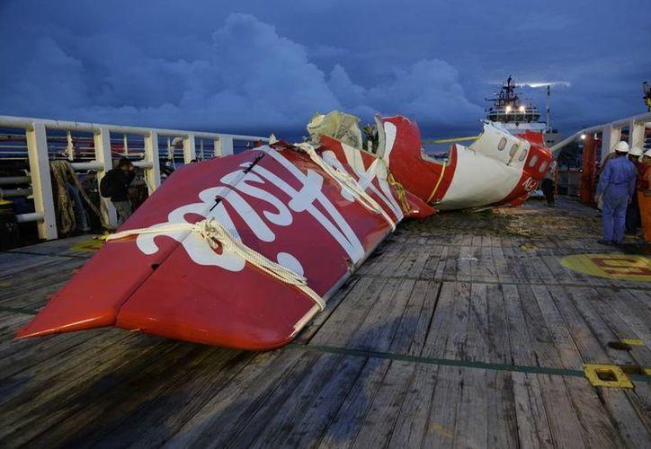 El sábado se rescató una pieza metálica de la cola del vuelo 8501 de AirAsia en el mar de Java. (AP)