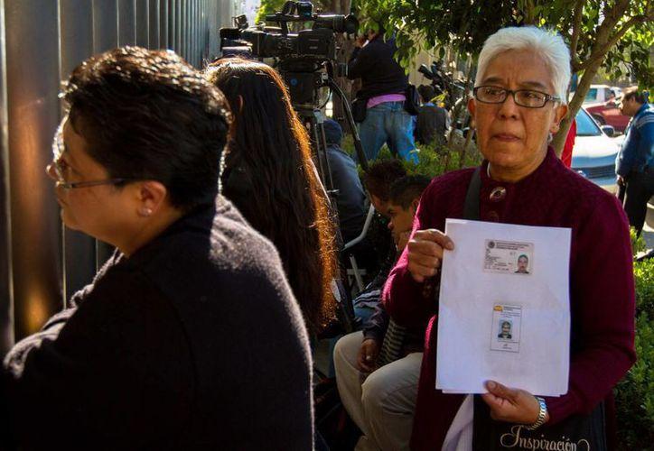 Familiares de los desaparecidos, esperan noticias atrás de las rejas de la torre de Pemex. (Notimex)